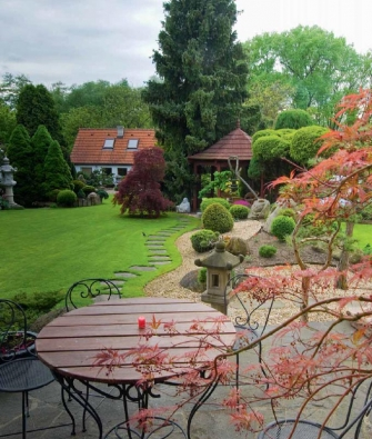 Pohled z terasy na střední část zahrady s čajovým domkem a dominantní Picea omorikou.