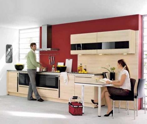 Kuchyňskou sestavu v provedení dekor světlého dřeva opticky člení pruhy černého skla aplikované na horních skříňkách a černé vestavné spotřebiče, cena od 148 000 Kč.