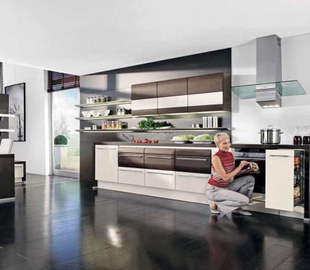 Strohost jednoduchých linií bílých ploch kuchyně z řady 7040 zjemňují zaoblené části s dekorem tmavého dřeva, cena sestavy od 235 000 Kč.
