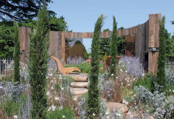 Vyvýšená terasa s výhledem využívá neopotřebované dřevěné pražce a ocelové dráty, obojí s náležitou patinou.