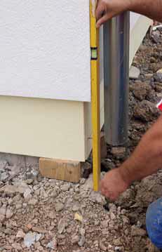 Kontrola rovinnosti fasádního povrchu, který musí být rovnoběžný s izolací soklu.
