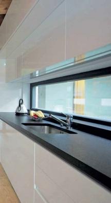 V teplých měsících se prostor obytné kuchyně rozšíří o atrium s jezírkem a dřevěným molem.