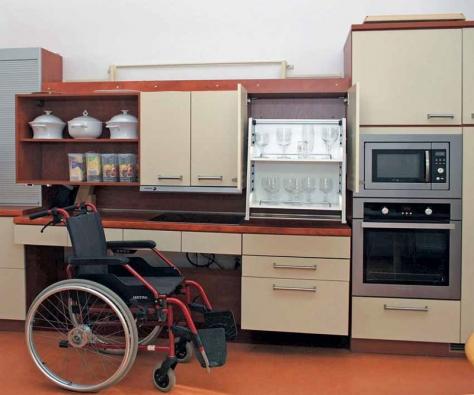 Kuchyňská sestava slouží v pražské Klinice rehabilitačního lékařství k nácviku soběstačnosti. Horní nábytkový díl i pracovní deska jsou výškově nastavitelné, horní police jsou vybavené sklápěcí konstrukcí. Individuální nastavení výšky umožňuje i deska se zabudovaným dřezem.