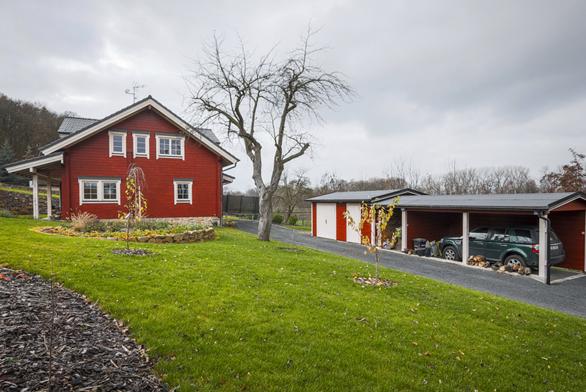 Pohled na dům od vjezdové brány ukazuje skvělou práci s barvami: falunská červeň je decentně doplněna světlou barvou sloupů, dveří a oken.