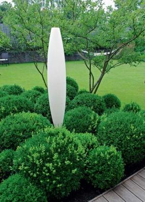 Pečlivě střižené buxusové kuličky u rodinného domu zvýrazňuje stylová stojací lampa. Stejný motiv se objevuje i v dalších částech zahrady. Kromě okrasných trav krášlí kulaté zimostrázy také muchovníky (Amelanchier lamarckii).