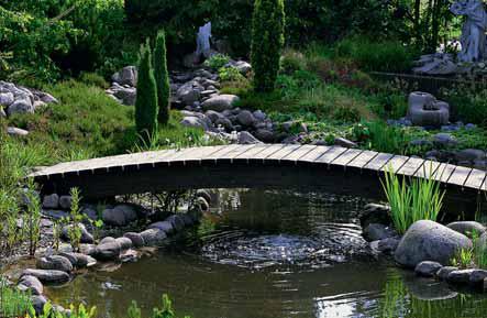 Klenuté dřevěné mostky patří svým tvaroslovím spíše k japonským nebo čínským zahradám.