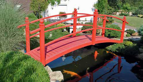 Z typické červené japonské lávky lze krmit koi kapry (symboly štěstí a úspěchu) a kochat se rozkvetlou flórou.