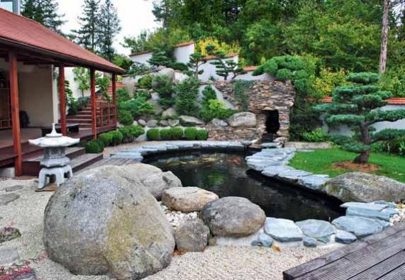 Spodní část Zahrady nad řekou se skálou a vodopádem, který stéká do jezera.
