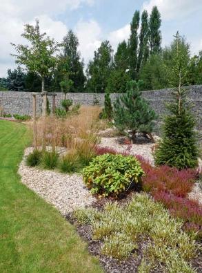 Výsadba na okrajích zahrady. Jehličnaté stromy (jedle, smrky a borovice) v kombinaci s okrasnými trávami, vřesy, pěnišníky a azalkami.