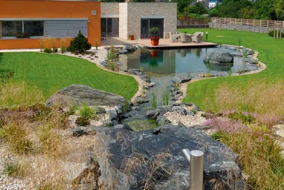 Celkový pohled přes jezírko na dům s terasou. Proporce jezírka jsou dimenzovány pro solidní plavání i potápění.