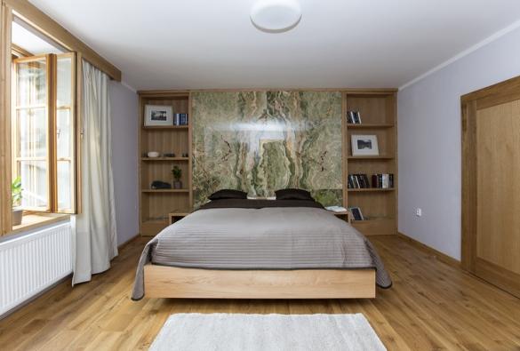 Dominantou ložnice je opět kámen, který je ze zadní části předsazené stěny nasvícený umělým světlem.