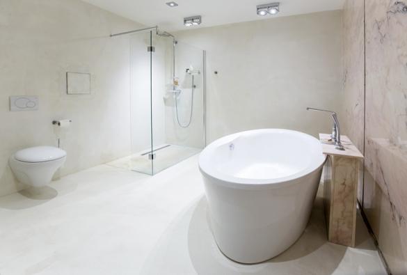 Koupelna má celou jednu stěnu obloženou růžovým onyxem, ke kterému designérka zvolila nenápadnou cementovou stěrku s nádechem slonové kosti.