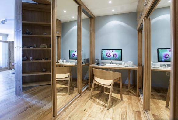 Na konci šatny je umístěn menší pracovní stůl Ema, který designérka navrhla jako limitovanou sérii pracovních stolů. Vrchní část stolu je z lacobelu, spodní část skla je prosvícena po obvodu LED páskem.