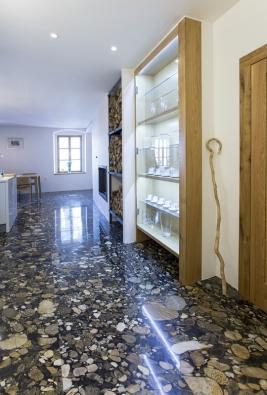 Kuchyň s chodbou propojuje krb, prostor na ukládání dřeva a skleněná vitrína, která zároveň slouží jako minigalerie.