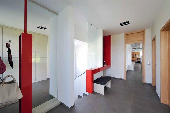 Členitá předsíň, která zahrnuje i schodiště, je vybavena atypickou sestavou skříněk z lakovaných MDF desek. Velká zrcadlová plocha pomáhá opticky zvětšit a prosvětlit prostor. Odkládací plochu se zásuvkami a sedátkem ocení zejména ženy, které nezanedbávají úpravu zevnějšku před odchodem z domu.