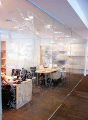 Monolitická celoskleněná příčka vyhotovená z tvrzeného čirého skla Planilux. Na skle je aplikován UV potisk, kterým lze tisknout jakýkoli motiv (SAINT-GOBAIN GLASS SOLUTIONS CZ).