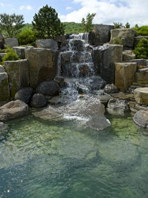 Dominantou horní části zahrady je velký vodopád sjezerem. Vpozadí památný vrch zvaný Koda.