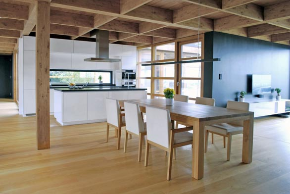 Díky proskleným plochám jsou osoby v kuchyni v kontaktu s hlavní obytnou částí i okolím domu. Architektonické řešení umožňuje vycházet do zahrady všemi směry.