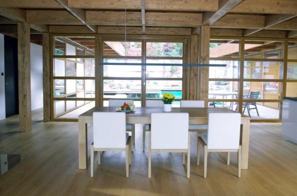 Masivní stůl byl zhotovený na zakázku, pohodlné židle (WESNER) mají dřevěnou konstrukci a jsou potažené bílou kůží.