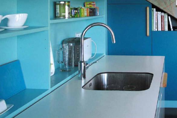 V této kuchyni v barvách mořské vody v kombinaci s přírodním dřevem, černými plochami a bílým pískovaným sklem se dobře vaří lidem, kteří mají rádi moderní design.