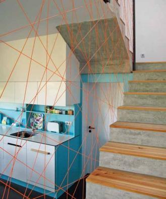 Betonové schodiště má nášlapy z olejovaného modřínového dřeva. originálním prvkem je dekorativní výplet.