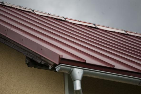 Špatný příklad kombinace kvalitní krytiny s levným plechem na hřebeni střechy. Životnost střechy se takovým krokem snižuje.