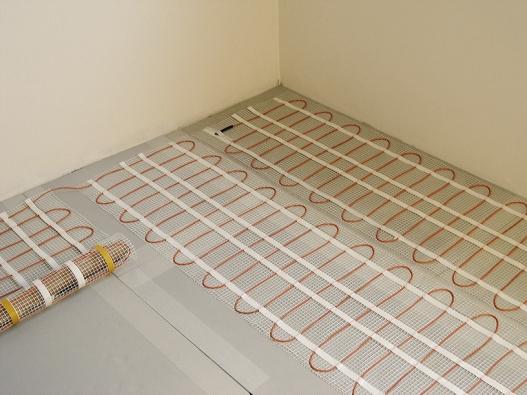Vysoký komfort bydlení vpasivním domě zajistí elektricky vytápěná podlaha, kterou lze snadno regulovat vkaždé místnosti. Vkombinaci srekuperací aslunečními paprsky umožní pružně reagovat namomentální tepelnou situaci (fenix).
