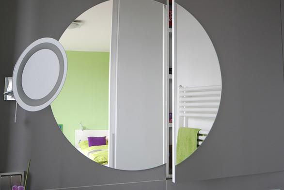 Pravá část kruhového zrcadla, za kterým je ukrytá polička, se otvírá isčástí stěny skeramickým obkladem.