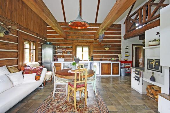 Uprostřed obytné kuchyně je starý jídelní stůl, který majitelka pořídila sdalšími kusy nábytku vbazaru.