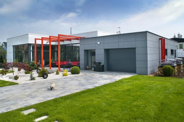 Kompozice domu je rozdělena nanižší hmotu garáže, obloženou cembonitem, aobytnou část svyšším stropem aobložením fasády zkompozitních panelů Alubond shliníkovým pláštěm.