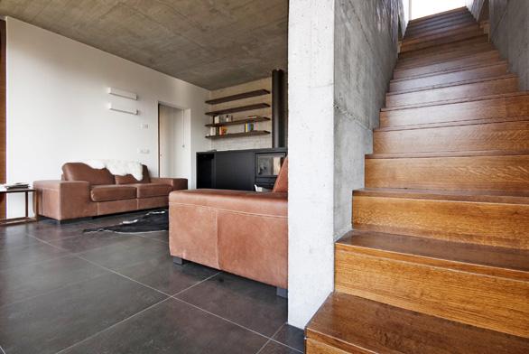 Obložení zpřírodního dřeva příjemně kontrastuje snosnou stěnou zpohledového betonu iskeramickou dlažbou.