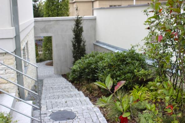 Mobilní nádoby zcortenu zpříjemňují vstup udomu adělají ho veselejším. Vpozadí dominanta zahrady – vysoký pyramidální habr (Carpinus betulus ´Fastigiata´).