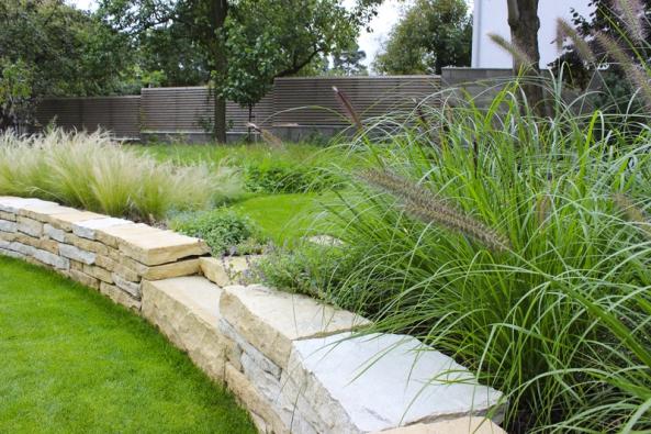 Suchá zídka zformátovaného kamene korespondující sobkladem domu. Tvoří předěl mezi reprezentativní částí zahrady avolnější převážně jedlou.