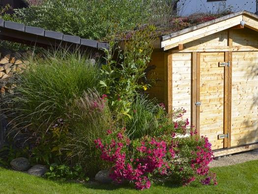 Zahradní domek má střechu osázenou hvozdíky, mateřídouškou, drobnými karafiátky, rozchodníky, netřesky,sama se vysela krásnoočka akoniklec. Mezi dřevníkem azahradním domkem je nádoba na dešťovku.