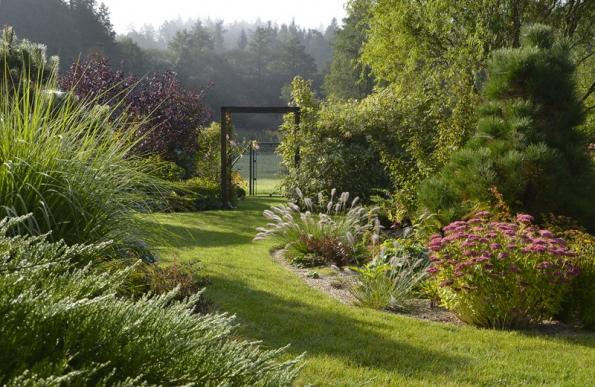 Ztrávníku se na několika místech stávají travnaté cestičky. Průchod do užitkové zahrady.