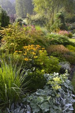 Vyvýšený záhon vystavěný formou suché zídky už není mezi rostlinami vidět. Pod ním je vřesoviště.