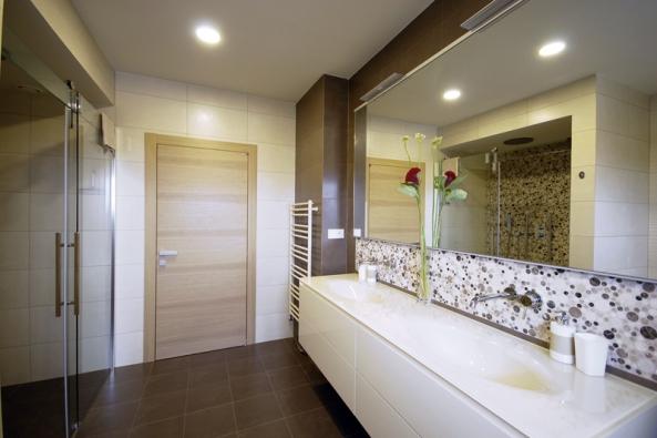 Vzrcadle se odráží sprchový kout, který je vybavený velkou hlavovou sprchou avertikálními masážními tyčemi (Bossini) určenými  k masáži voblasti beder, které nahradí masivnější masážní panel.