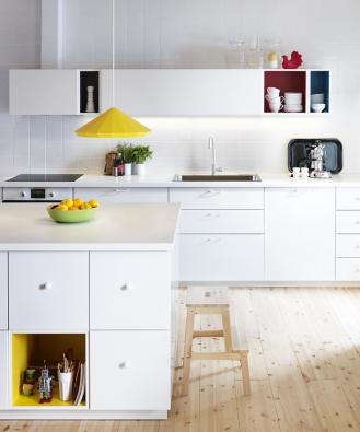 Kuchyň Metod (Ikea) sdvířky ačely zásuvek Veddinge, zásuvky Maximera aotevřené skříňky Tutemo. Dvířka ačela zásuvek mají lakovaný povrch, zajímavostí jsou otevřené skříňky  s barevným lakovaným povrchem všedé, červené, světle modré nebožluté barvě. Úchytky jsou zlakované oceli Ulvsbo, linka je opatřena bílou laminátovou pracovní deskou Personlig, cena této kombinace (dva bloky linky 220 a400cm + kuchyňský ostrůvek) 84746Kč, cena spotřebičů 40950Kč.