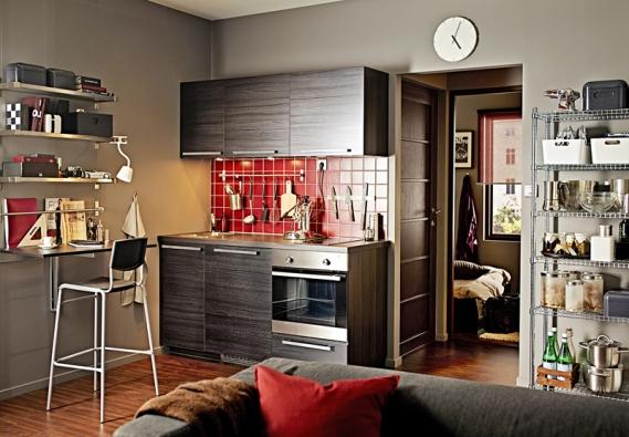 Minimalistická, ale plně vybavená kuchyň Metod (Ikea) do malého prostoru. Dvířka ačela zásuvek – fólie s dekorem černého dřeva, pochromované hliníkové úchytky Ekeboda, oboustranná laminátová pracovní deska Ekbacken sčernohnědou hranou, cena této kombinace 8867Kč, trouba Görlig, cena 3990Kč.