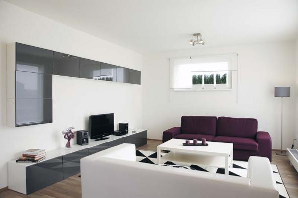 Také interiér vzorového domu je navržen vestylu střízlivé elegance. Otevřená společná obývací část působí nanávštěvníky příjemným vzdušným aprostorným dojmem. Napodlaze sdezénem světlého dřeva vynikne černobílý koberec inábytek zlakovaných MDF desek.
