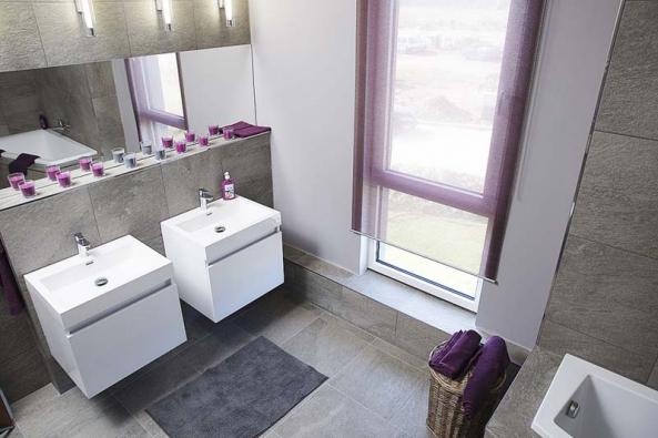"""Také koupelny """"drží"""" šedobílou linii. Kontrast bílé sanitární techniky aobkladu sdezénem světlého kamene působí vzdušně aluxusně."""