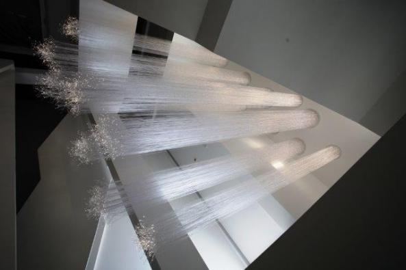 Schodišťovým prostorem prochází kinetická plastika zoptických  vláken, která se nejen půvabně vlní, ale také svítí.  Vyrobila společnost Lasvit, design Maxim Velčovský.