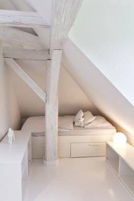 Postel je schována za sloupkem,  v zákoutí pod šikmým stropem.