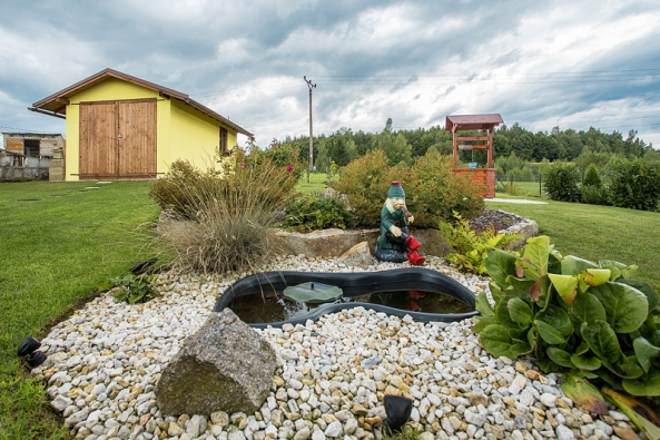 Úplně vzadu vrohu stojí také garáž, kterou ale majitelé využívají spíše jako sklad zahradního nářadí. Kdomu přiléhá ipoměrně velká zahrada, osázená zejména ozdobnými rostlinami. Zahradu nechávají okrasnou, nicméně tu stejně najdete bylinky dokuchyně. Plochu zadní části zahrady tvoří hlavně trávník, ale našlo se zde místo inamalé jezírko spanem vodníkem.