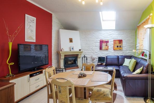 Obývací pokoj spojený skuchyní prošel oddokončení již několika změnami. Například místo původní bílé výmalby stěn se majitelé rozhodli pro pestré barvy, které si mohli vdobře prosvětleném interiéru dovolit.