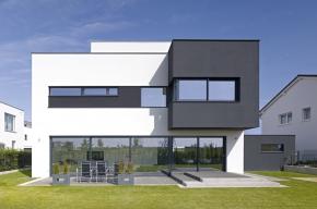 Fasáda orientovaná do zahrady: Posuvné dveře, pevné zasklení a okenní pásy vytvářejí horizontální zářez do černých a bílých bloků fasády.