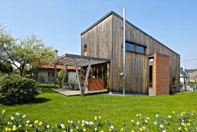 Dřevěný hranol s pultovou střechou cituje nízký severní svah a stoupá od příjezdové cesty směrem do zahrady, ke slunci otevřené jižní terase.