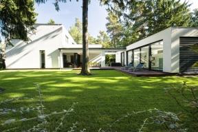 Rozlehlý pozemek umožnil architektům zvolit velkorysé řešení – koncept vychází ze vzájemného propojení čtyř kubických hmot vdynamické ose stočené dopísmene S.