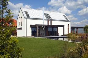 Moderní dům se sedlovou střechou je úzce provázaný francouzskými okny se zahradou. Rozlehlá terasa zastřešená pergolou orientovaná najih se zahezkých dní stává dalším obytným prostorem spřímou návazností nazahradu ajezírko.