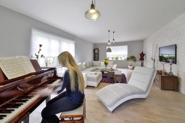 Vodpočinkové části obývacího pokoje anad křídlem jsou zavěšená svítidla Shadows odBrokis. Soukromí zajišťují lamelové rolety Silhouette vkombinaci měkké tkaniny aprůsvitného materiálu, které lze zakoupit např. veStyltexu.